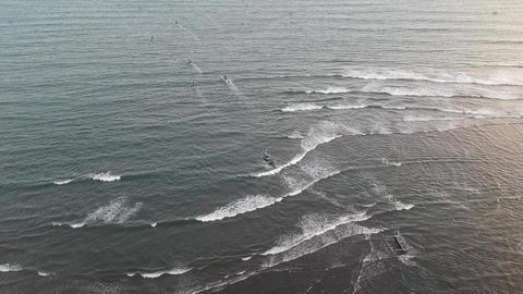 fishermen swim chopping through large waves, the camera pans to the horizon Live Action