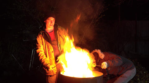 Two homeless young men are frying potatoes on a fire. Men stand at night near a Live Action