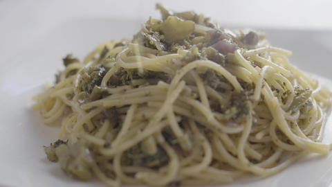Close-up of a steaming plate of vegan spaghetti with broccoli and capers and a drizzle of extra Live Action