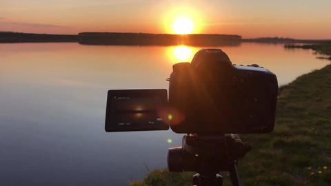 Camera shoots timelapse sunset over the sea on tripod. Review of camera making Live Action