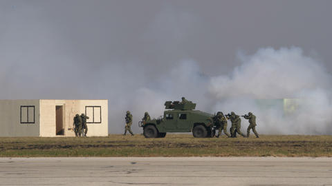 Soldiers walk covered by an humvee and an anti riots vehicle on the battlefield Live Action