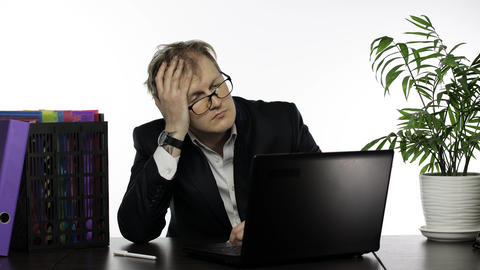 Tired disheveled businessman working hard in office on laptop at the office desk Live Action