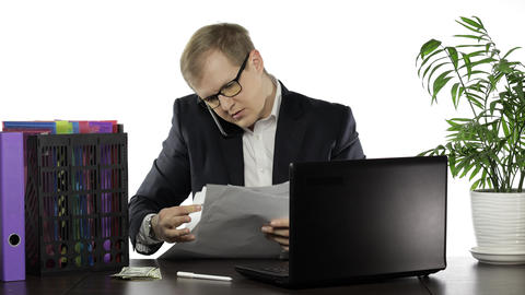 Businessman working in office. Talking loudly on telephone while reading papers Live Action