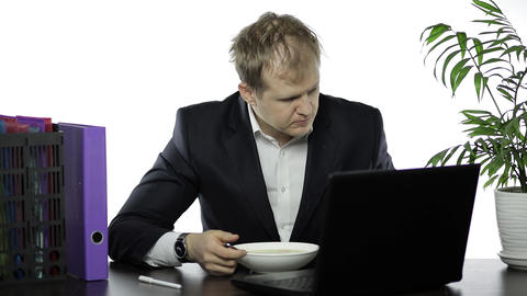 Disheveled businessman working in office having a lunch at the office desk Live Action