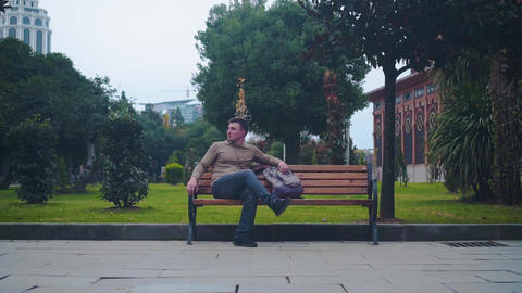 A man is sitting alone on a bench in an empty city and is…, Live Action