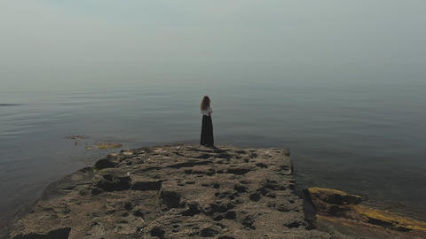 Aerial drone footage of woman standing on rocky beachside view from back Live Action