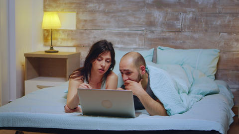 Couple wearing pajamas lying in bed Live Action