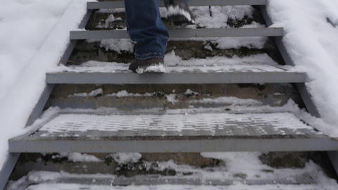Man climbs a snow-covered metal staircase Live Action