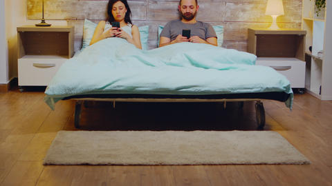 Bored young couple in pajamas using smartphone Live Action