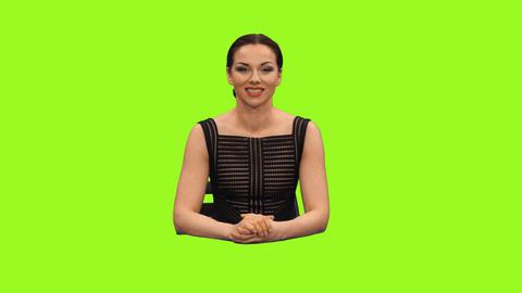 Female news reporter sitting in a studio & talking, alpha channel Footage