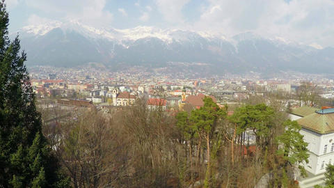 Beautiful aerial view of big city at bottom of Austrian Alps, snow on mountains Footage
