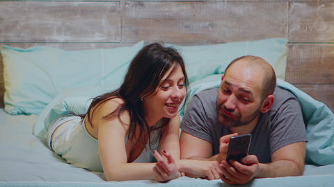 Wife in pajamas laughing while her husband is showing something on phone Live Action