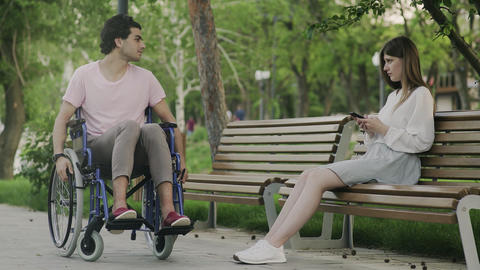 Young man in a wheelchair trys to meet woman in the park. Woman dont talk with Live Action