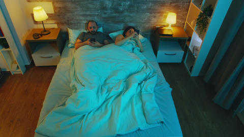 Top view of couple in the bedroom late at night using their phones Live Action