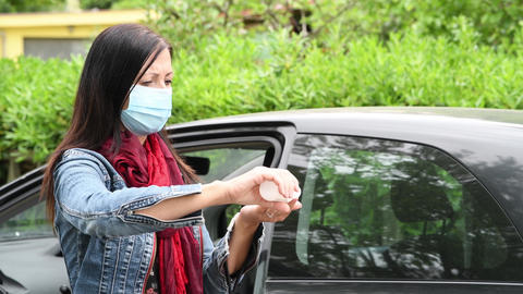 Woman taking groceries from her car disinfecting hands and wearing mask from Live Action