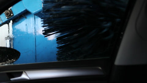The car in the car wash washes brushes against the background of blue equipment Live Action