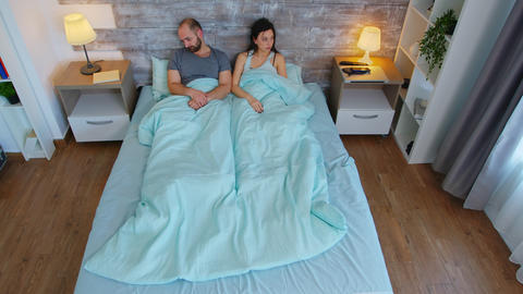 Top view of young couple under the bed sheets in the morning Live Action