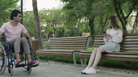 Young man in a wheelchair rides in park and young woman sits on bench and look Live Action