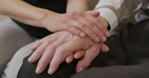 A young womans hands comforting a old man hands. Closeup Live Action