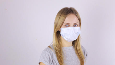 A girl in a protective mask rubs her eyes with her hands Live Action