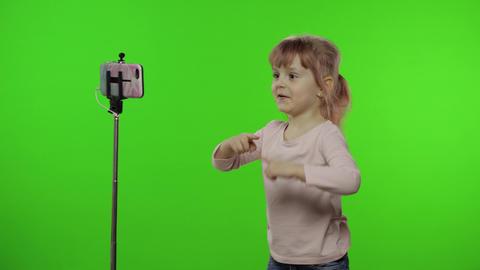 Girl child makes selfie vlog, blogging, video call on mobile phone using monopod Live Action