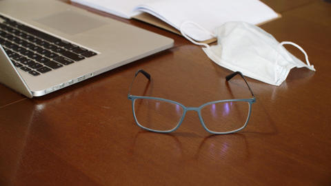 Glasses on wooden table on laptop, protective mask and daily planner background GIF
