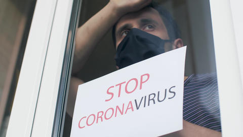 Stop coronavirus. Man holding a sign outside the window Live Action