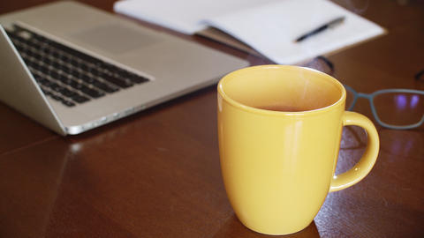 Close up yellow cup with hot tea and steam on laptop and glasses on wooden table GIF
