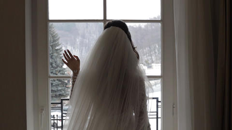 Beautiful, lovely bride in wedding luxury dress and veil. Stay near window Live Action
