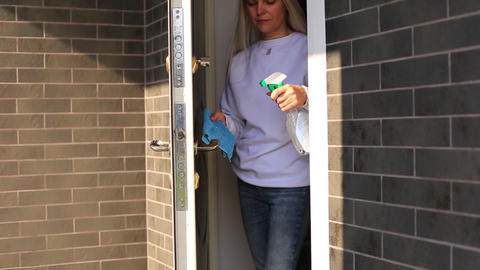 Young girl disinfects the door handle Live Action