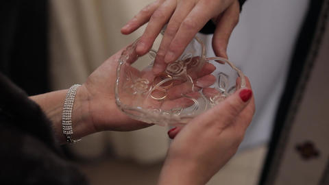 wedding rings in plate with holy water during matrimony. priest takes one ring Live Action