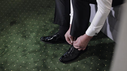 Hands of groom putting his wedding shoes on wedding day. Wedding day Live Action