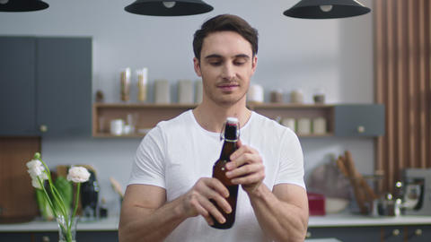 Portrait of joyful man opening beer at home kitchen. Young man enjoying alcohol Live Action