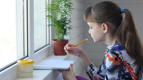 Girl draws by the window with a pencil in an album Live Action