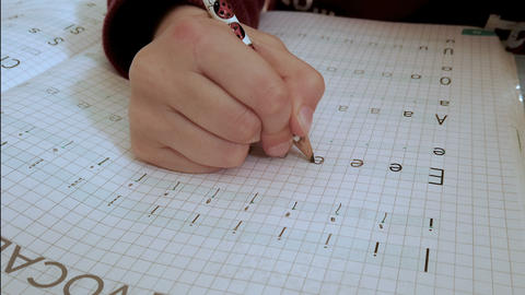 Close up of primary school kid hand while doing homework writing, excercise book Live Action