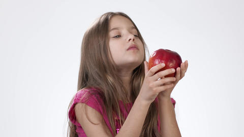 Little girl on white eats a big red apple. A girl bites a piece of red ash and Live Action