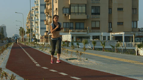 Slim lady jogging along urban road. Active lifestyle for wellness and health Footage