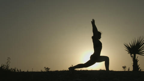 Silhouette of active woman practicing yoga positions, doing exercises at sunset Footage