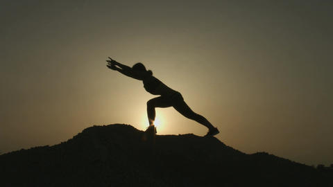Woman with flexible body practicing yoga positions, doing exercises in mountains Footage
