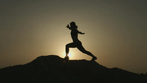Silhouette of woman practicing yoga alone on top of mountain in the evening Footage