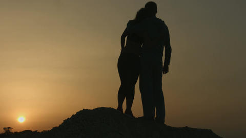Man hugging woman at romantic date. Couple looking at amazing sunset together Footage