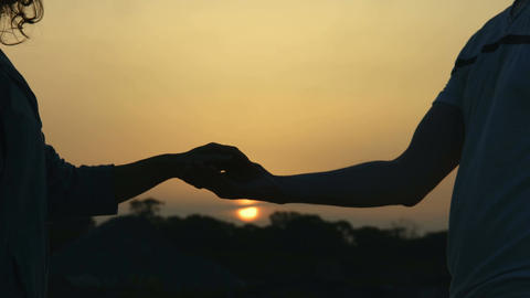 Man touching beloved woman's hand. Romantic proposal at sunset. Magic hour Footage