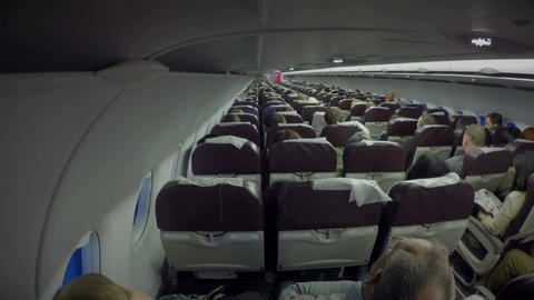 Economy class passengers sitting inside plane cabin. Air transport services Footage