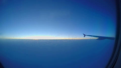 Passenger airliner flying at thousands feet height. Sun rising through clouds Footage