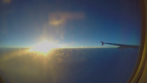 Airplane flying high in sky. Passenger looking at cloudscape through porthole Footage