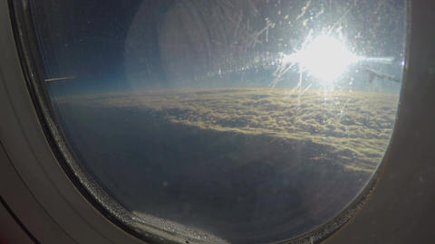 View of sun shining over cloudscape through dirty window of plane flying in sky Footage