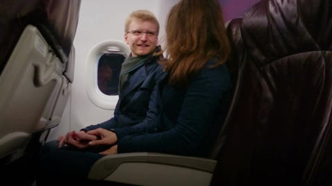 Happy young man and woman flying on plane with comfort, holding hands, talking Footage