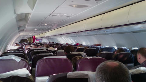 People flying on board of economy class passenger plane. Aircraft in turbulence Footage