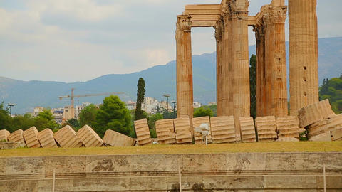 Remains of ancient Olympian Zeus Temple corner, modern Athens in background Footage