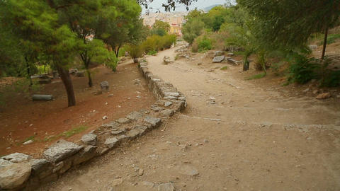 Ancient stony road through park to modern city, decaying old infrastructure Live Action
